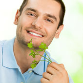Young smiling man with potherbs — Stock Photo