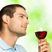 Young man with glass of redwine, outdoors — Stock Photo