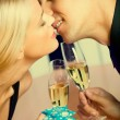 Couple with champagne and gift, kissing at party — Stock Photo #47957863