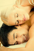 Young attractive happy amorous couple at bedroom — Stock Photo