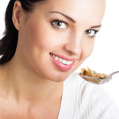 Woman eating muesli or cornflakes, isolated  — Stock Photo