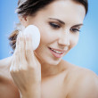 Young woman cleaning skin by cotton pad, over blue — Stock Photo #48418945