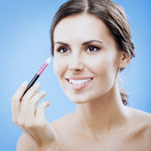 Woman with cosmetics brush, on blue — Stock Photo