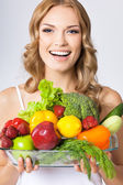 Young woman with vegetarian food, over gray — Stockfoto