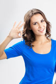 Young woman showing okay gesture, over grey — Stock Photo