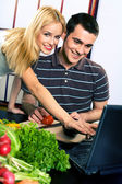 Young happy couple cooking at kitchen with laptop — Стоковое фото