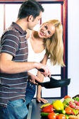 Young attractive happy smiling couple playfully cooking at kitch — Stock Photo