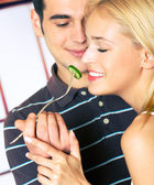 Young happy couple playfully eating, indoors. Focus on woman. — Стоковое фото
