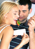 Young attractive happy smiling couple eating playfully vegetable — Stock Photo