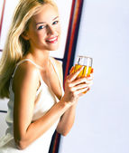 Young attractive blond woman with glass of juice indoors — Stok fotoğraf