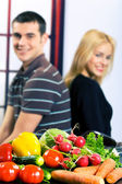 Vegetables on the table and blurred young happy smiling couple o — Stock Photo