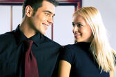 Young attractive smiling couple or business people — Stock Photo