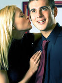 Young attractive smiling couple or business people kissing — Stock Photo