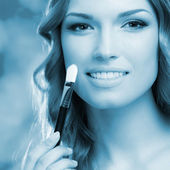 Smiling woman with make up brush — Stock Photo