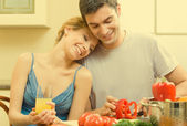 Cheerful young cooking couple at home — Stok fotoğraf