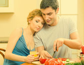 Cheerful young cooking couple at home — Stock Photo