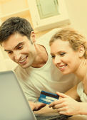 Cheerful couple paying by plastic card — Stockfoto