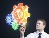 Man drawing color gears — Stock Photo