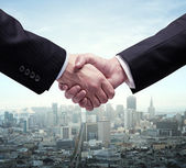 Handshake and city — Stock Photo