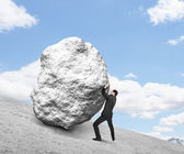 Businessman pushing stone — Foto Stock