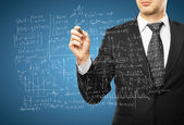 Man drawing mathematical formulas — Stock Photo