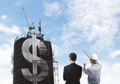 Builder and skyscraper with dollar — Stock Photo