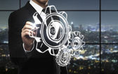 Businessman drawing gears — Stock fotografie