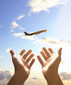 Hands reach for airplane — Stock Photo