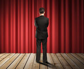 Businessman looking to red curtains — Stock Photo