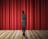 Woman looking to red curtain — Stockfoto