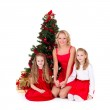 Mother with children sit near Christmas tree. — Stock Photo #6765613