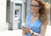 Woman on street with smartphone — Stock Photo