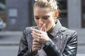 Beautiful woman smokes a cigarette on the street — Stock Photo