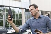 Man holding i-pad tablet computer — Stock Photo