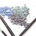 Crushed eyeshadow with makeup brushes — Stock Photo
