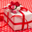 White gift box with red bow and paper flowers - Stock Photo