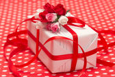 White gift box with red bow and paper flowers — Stock Photo