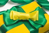 Yellow gift box with green ribbon — Stock Photo