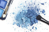 Crushed blue eyeshadow with makeup brush — Stock Photo
