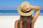 Girl holding the hat with the beach background — Stock Photo