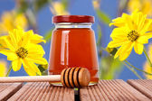 Natural honey with yellow flowers — Stock Photo