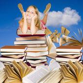Girl on piles of books — Stock Photo