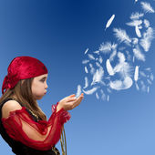 Young girl blowing feathers — Stock Photo