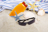 Stars, toalla y protector solar en la playa — Stock Photo