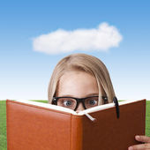 Girl reading with blue sky — Stock Photo
