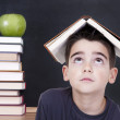 Young boy with book on his head and stacked books — Stock Photo