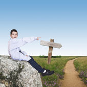 Boy sitting on the stone indicating the direction of travel — Stock Photo