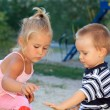 Lovely little children playing in sandbox — Stock Photo #14816293