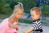 Lovely little children playing in the sandbox — Stock Photo