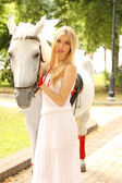 Beautiful lady with white horse — Stock Photo